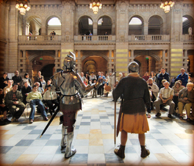 armoured knight speaking to audience in magnificent hall